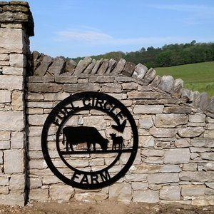 Full Circle Farm Sign witch a Cow and Calf mounted to a stone entryway